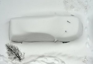 A snow covered car is seen from the roof of a building in Washington on January 23, 2016. A deadly blizzard with bone-chilling winds and potentially record-breaking snowfall slammed the eastern US on Saturday, as officials urged millions in the storm's path to seek shelter -- warning the worst is yet to come. US news reports said at least eight people had died by late Friday from causes related to the monster snowstorm, which is expected to last until early Sunday.   / AFP / Mladen ANTONOV        (Photo credit should read MLADEN ANTONOV/AFP/Getty Images)